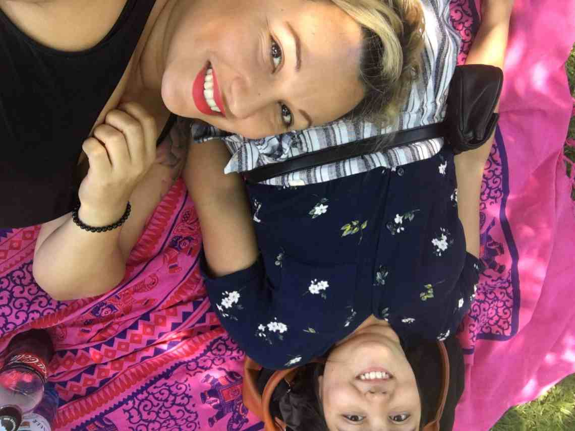 mother and daughter laying on a blanket