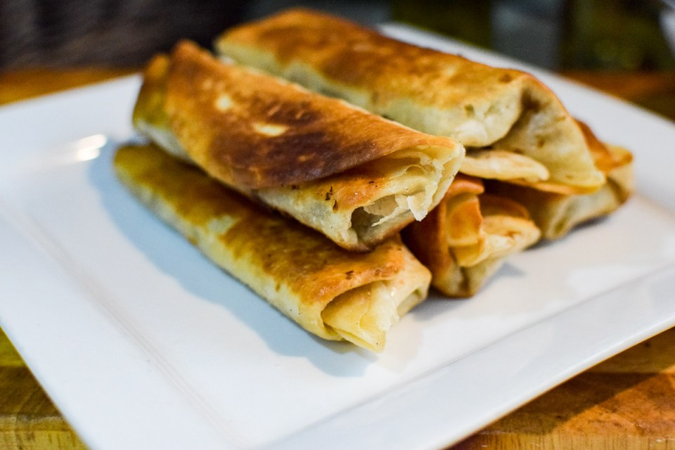 chicken and grilled onion taquitos on a white platter