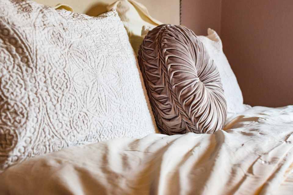 a bed made with cream and pink accents preppingfor fall