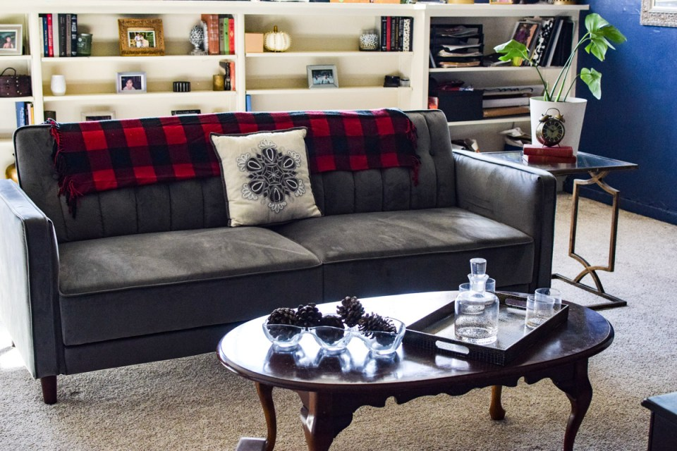prepping for fall with a a couch with flannel, pine cones and a coffee table \