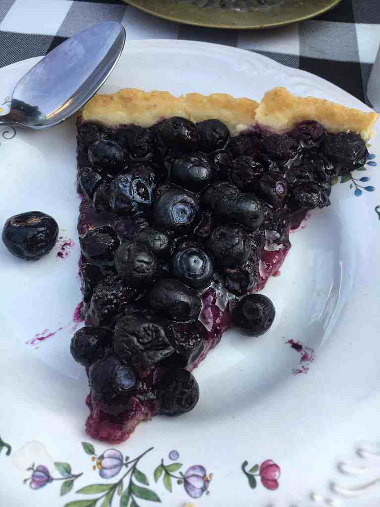 blueberry tart on a floral plate practicing hospitality