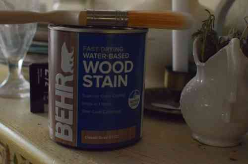a can of behr wood stain and a paint brush