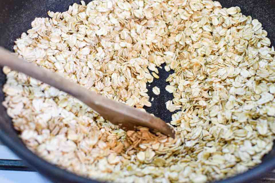 skillet with oats and a wooden spoon