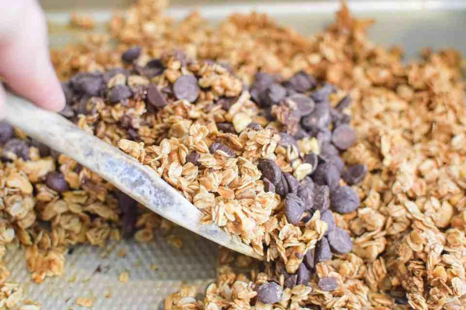 a spatula mixing chocolate and walnut granola