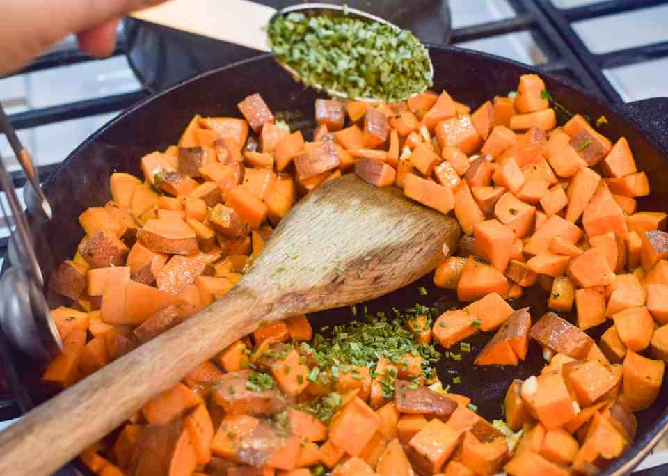 sweet potatoes inside a skilled with chives