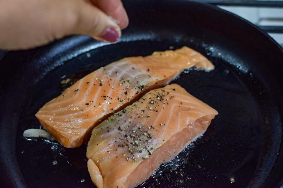 seasoning salmon while it cooks in the pan