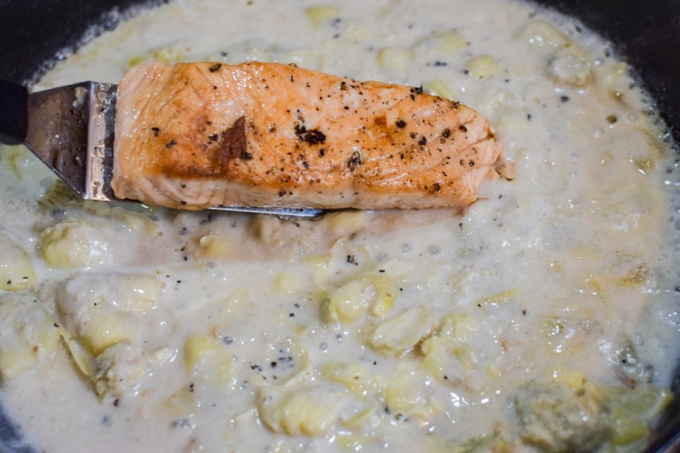 salmon being placed into artichoke cream sauce