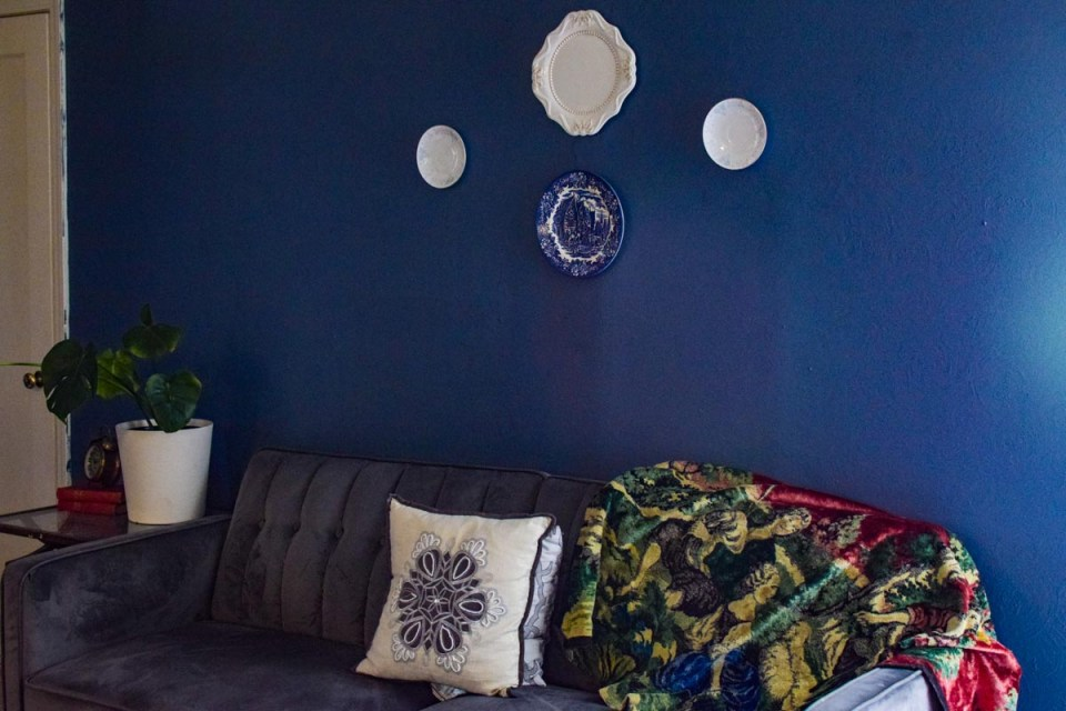 showing a blue wall with vintage plates hanging