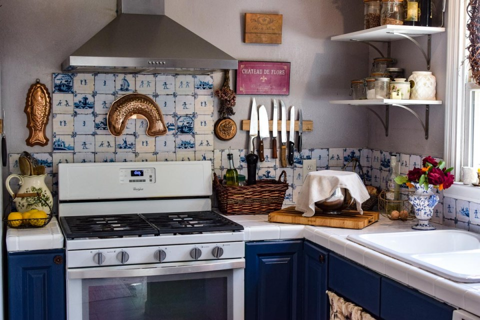 a blue kitchen with copper creates a french or old world farmhouse look