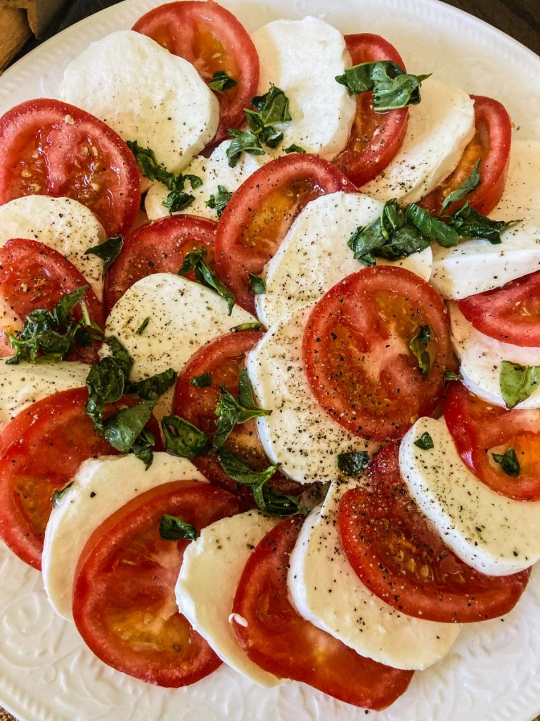 easy foods to entertain with is a mozzerella and tomatoes on a platter