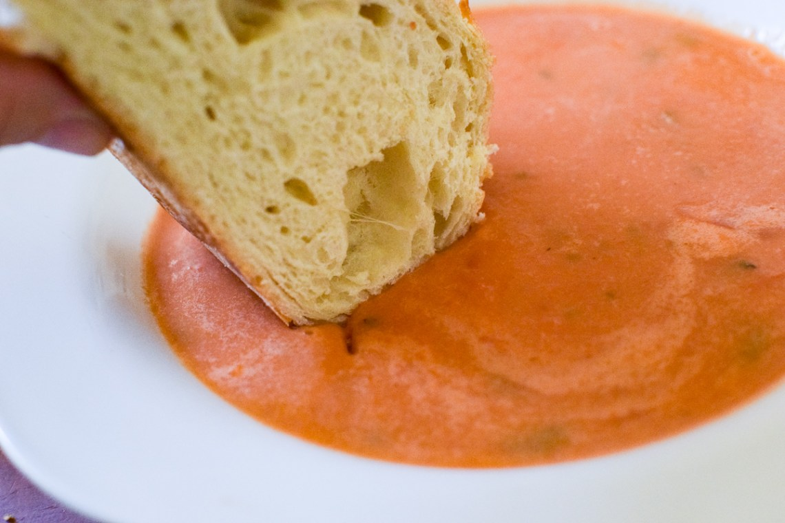 creamy tomato pesto soup in a white bowl