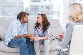 Couple looking to each other during therapy session while therap
