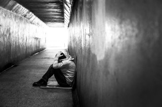 Homeless young man sitting on the floor of a subway tunnel with his head in his hands. He is wearing a grey hooded sweatshirt and a black beanie hat to protect him from the cold winter weather. Horizontal, toned black and white image with copy space.