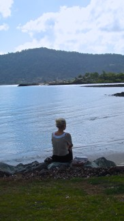 A young woman watches the morning roll in near the shore of Airlie Beach. Photo by: Leviana Coccia.