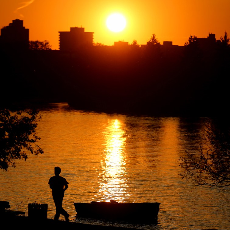 Jogger in front of the setting sun near the Canoe and Kayak Club on the Red River. Photo by Trevor Hagan. @wpgphotog/@everydaywinnipeg