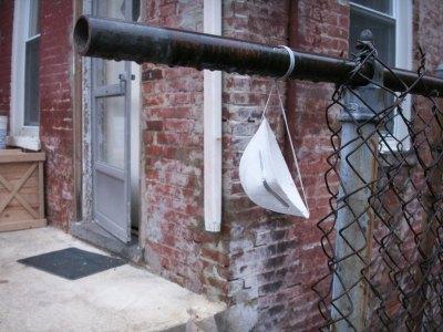 Mascarilla abandonada en una tubería, junto a una verja, en una ciudad.
