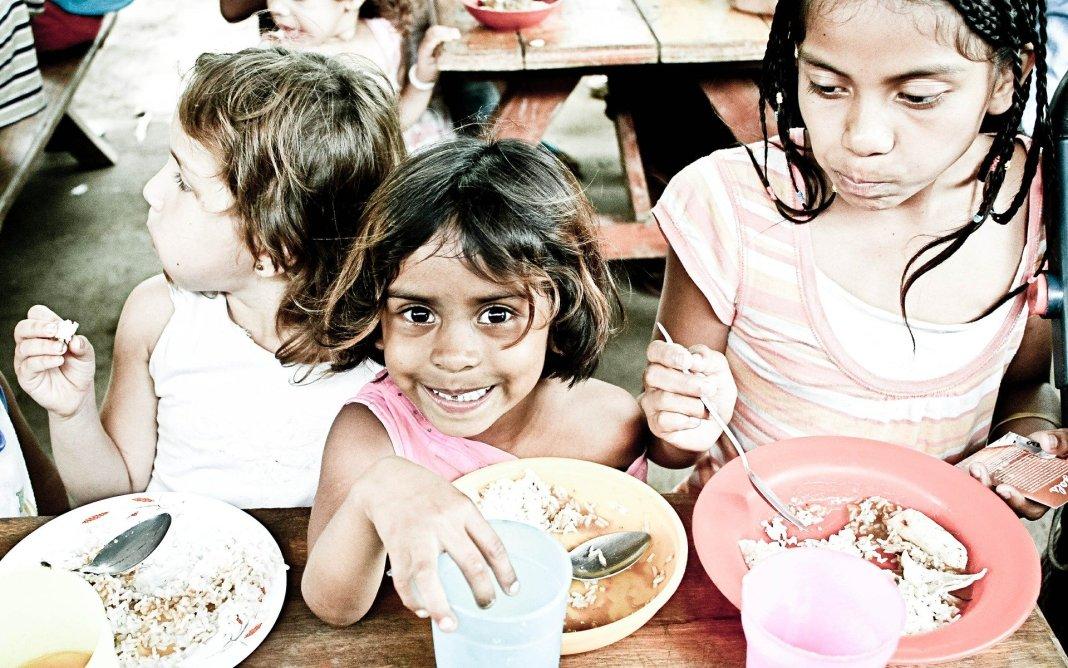 Niñas pobres comen en un comedor escolar.