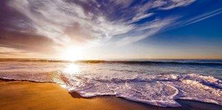 Las olas, espumosas, rozan la arena de la playa durante una puesta de sol,