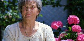 Mujer mayor con unas flores detrás.