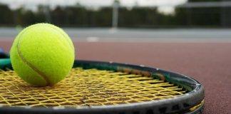 Raqueta de tenis apoyada en el suelo de una pista, con una pelota encima.