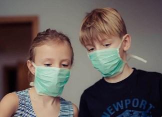 Una niña y un niño con mascarilla