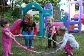 Daycare Children Playing with a Hula Hoop at A Quiet Forest Daycare and Preschool in Duvall WA