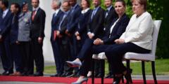 ميركل تجلس على كرسي خلال مراسم استقبال في برلين