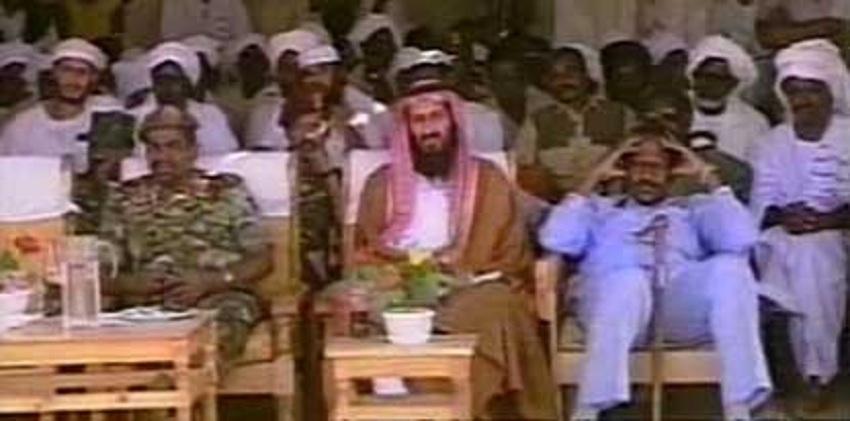 الزعيم السابق لتنظيم القاعدة أسامة بن لادن (وسط) جالسًا بجوار الرئيس السوداني السابق عمر البشير (يسار) في الخرطوم عام 1998. [صورة أرشيفية]