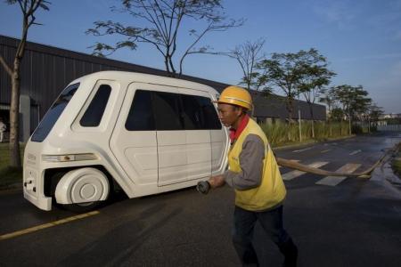 صورة من أرشيف رويترز لعمل يمشي بجوار مركبة تسير سائق في مركز أبحاث في مدينة دونغقوان في مقاطعة قوانغدونغ في جنوب الصين.