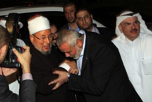 هنية يقبل يد القرضاوي خلال زيارته غزة