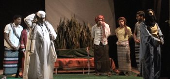 Courtroom scene from the 2013 Yemeni adaptation of The Merchant of Venice. Foreground: the judge, perplexed, in white; Fitna [Portia] in disguise in blue and yellow. Photo by Wagdi Al-Maqtari, courtesy of YALI/Akram Mubarak.