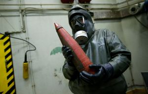 A worker dressed in protective clothing holds a dummy chemical grenade during a demonstration at GEKA  in Munster