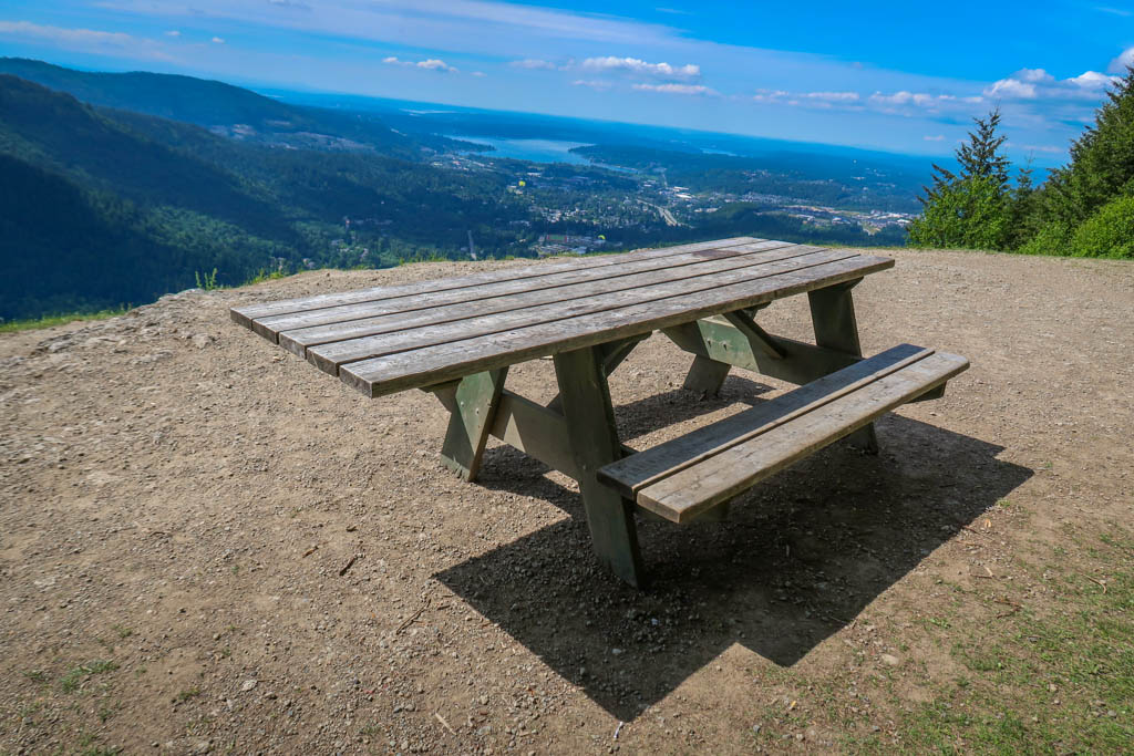 Picnic table at Poo Poo point with view of Puget Sound in the background