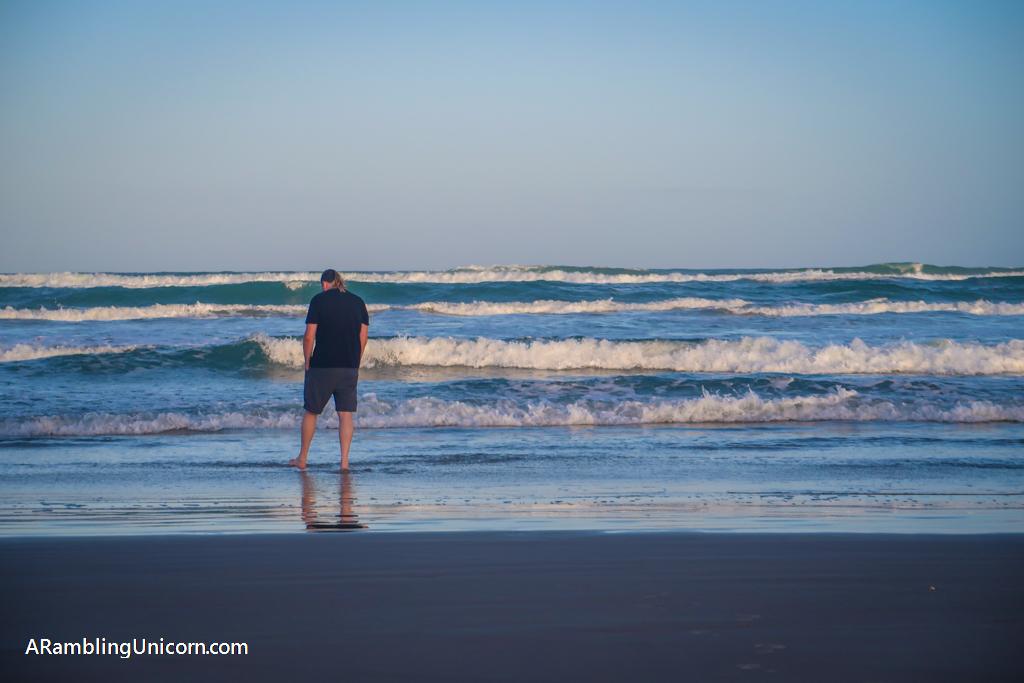 Daniel dips his toes in the ocean