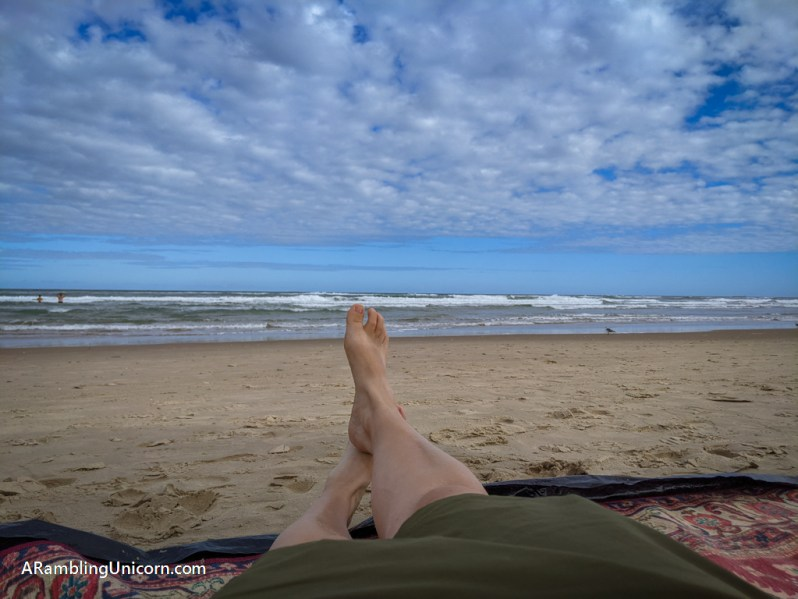 Photo of the beach with the waves in the distance. My bare feet are all I can see in front of me.