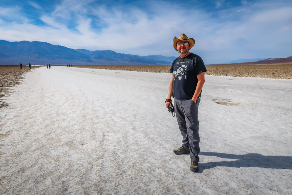 Daniel walks on the Death Valley salt flats on a trail which is comprised of a wide path of crushed white salt and other dried minerals.