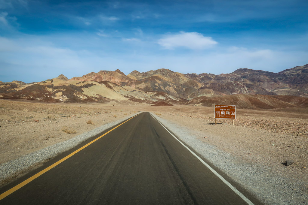 The road in Death Valley stretches ahead with colorful hills in the distance streaked with various vivid shades of brown and white and red. These are the Artist's Palette.