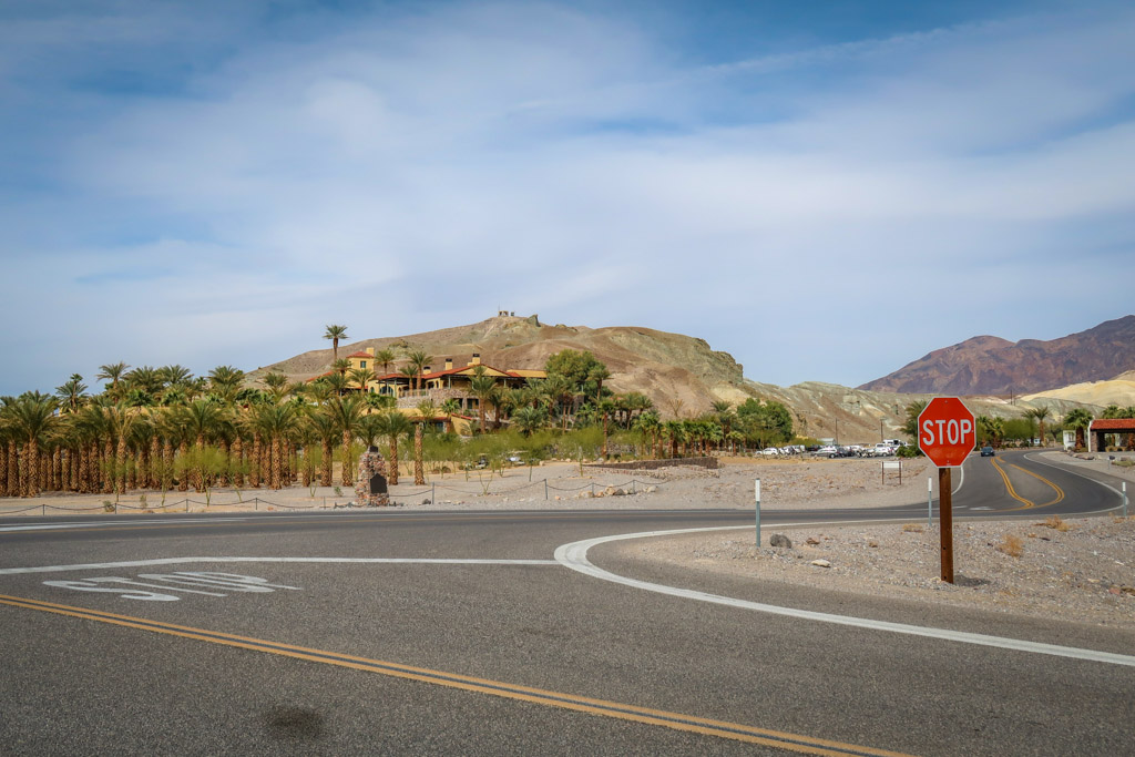 Intersection at Death Valley National Park with palm trees and a hotel in the background