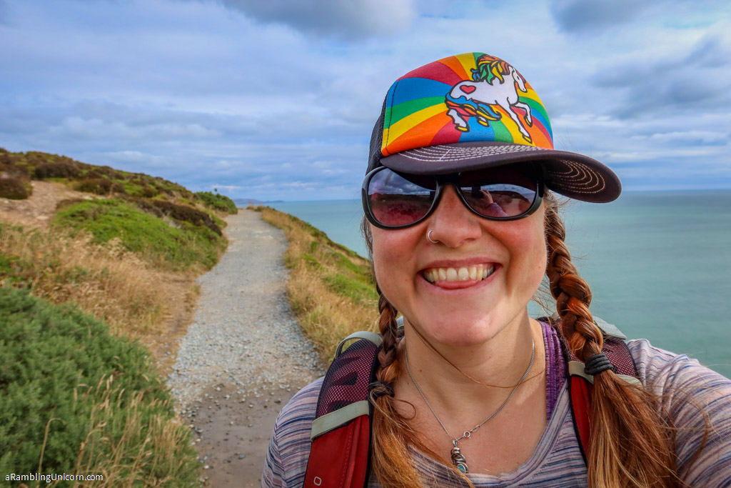 Selfie of the author in a rainbow unicorn hat on the Howth Cliff Walk