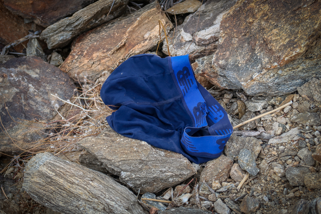 A bright blue pair of mens underpants on the ground next to the trail