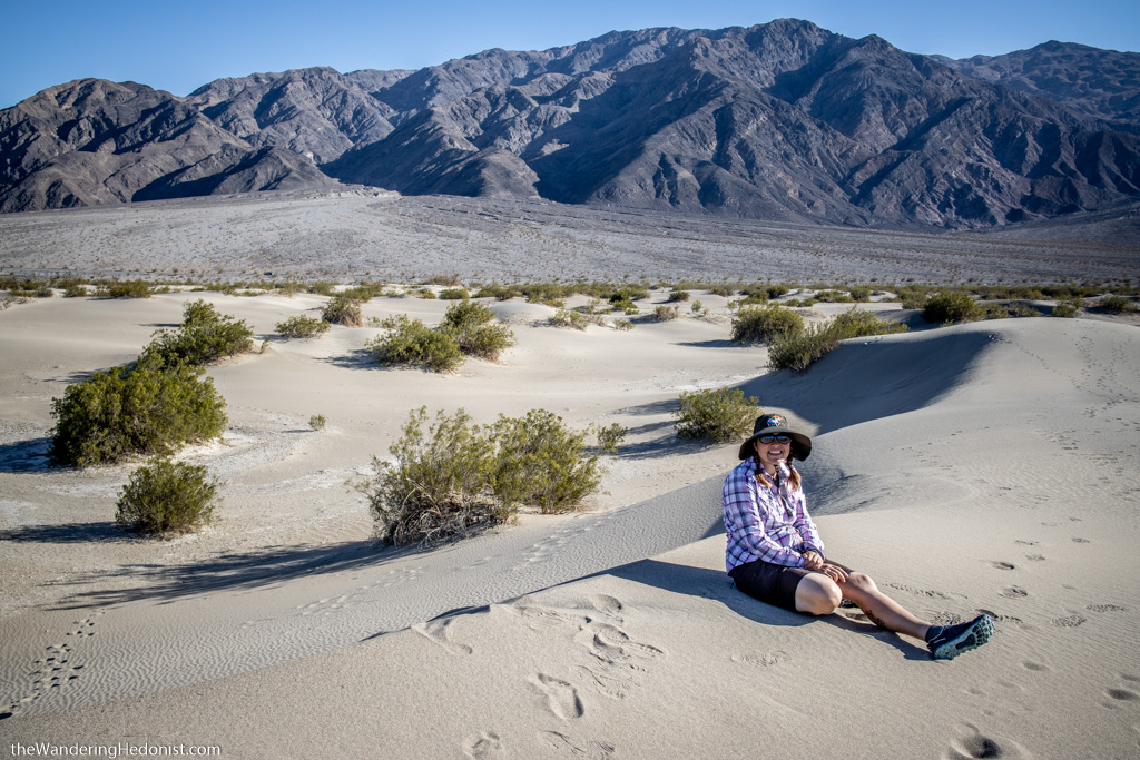The author sits on a sand dune at Death Valley National Park. She is wearing a broad sun hat with a unicorn on it.