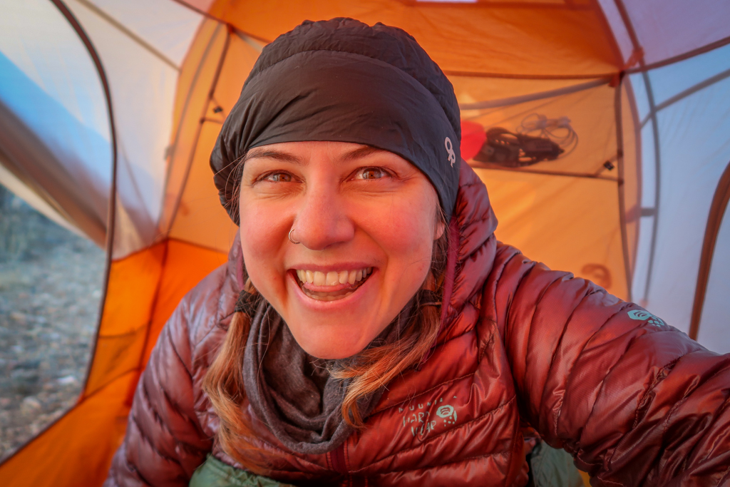 Photo of the author in her tent, bundled up with a down hat and down coat.