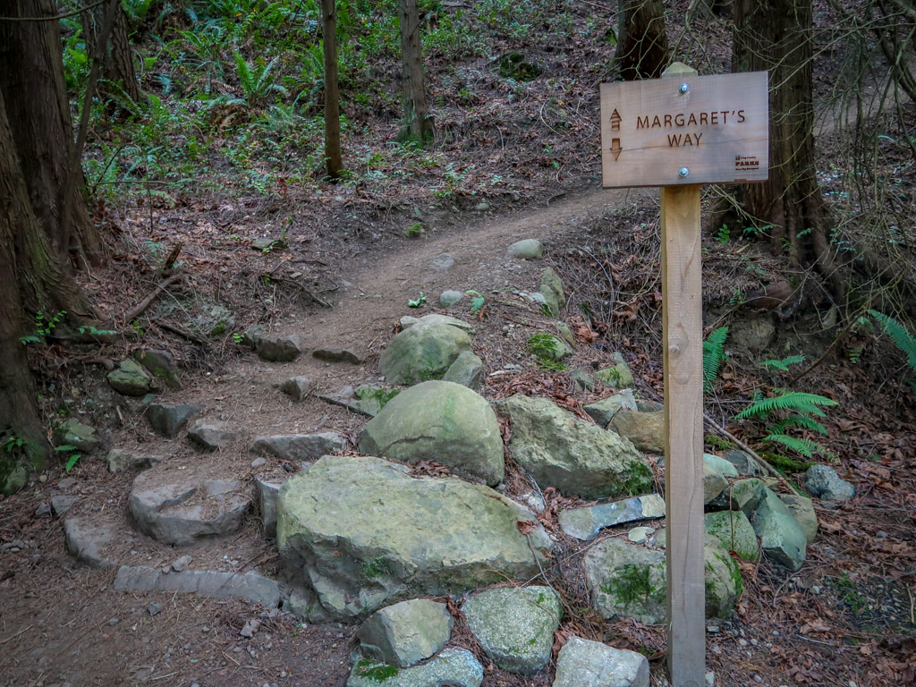 """A signpost reading """"Margaret's Way"""" stands next to a hiking path that leads up into the woods"""