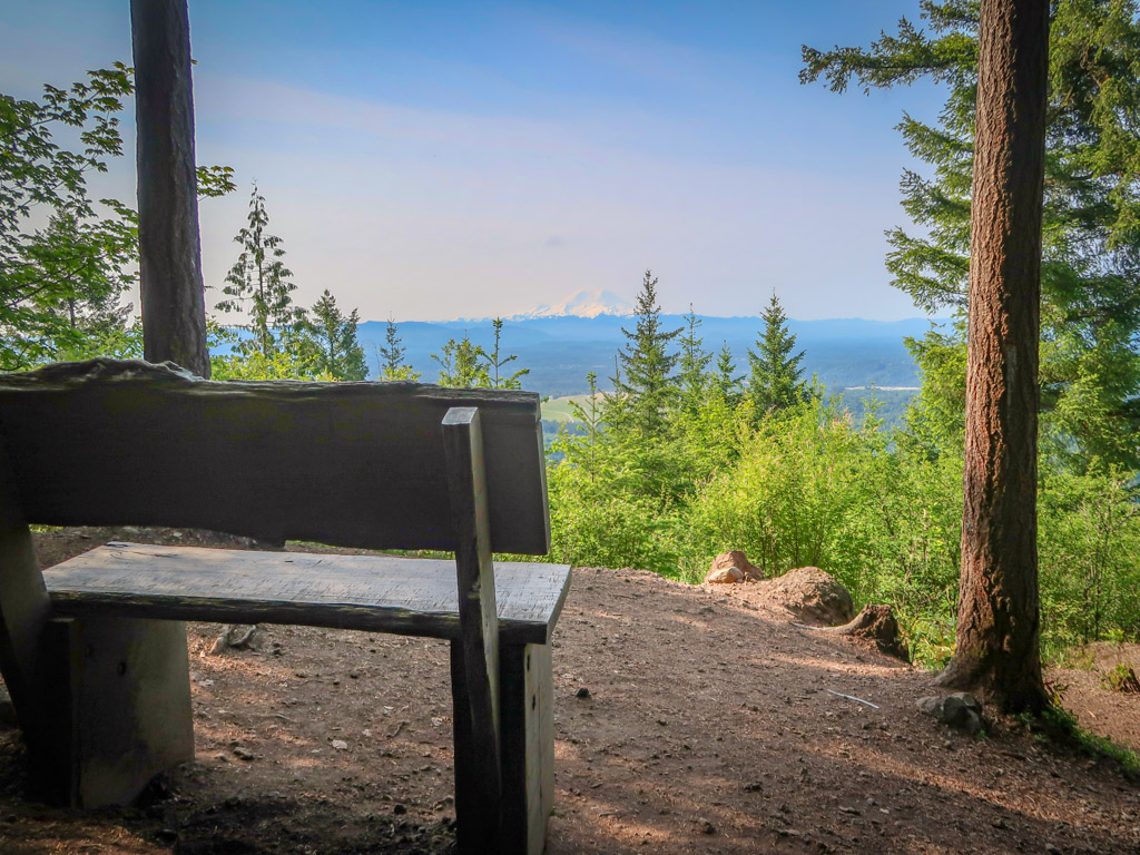 A bench at Debbie's View sits facing a vista with Mt. Rainier poking above the clouds in the distance