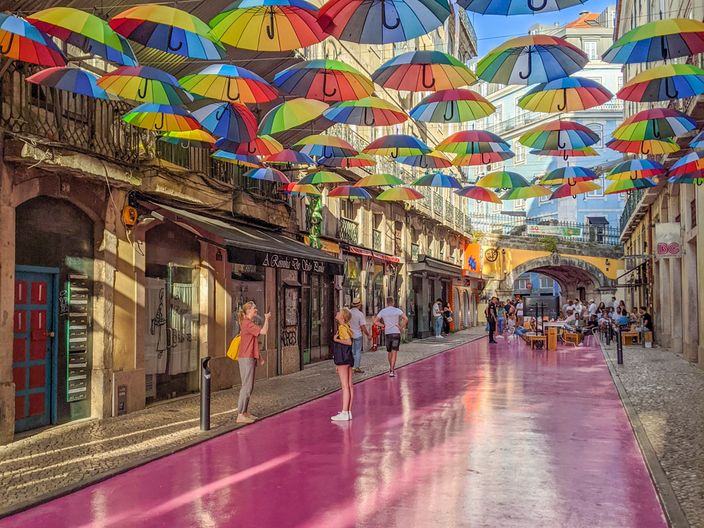 Brightly-colored rainbow-striped umbrellas are strung across a street painted bright street an an alley lined with shops and cafes.
