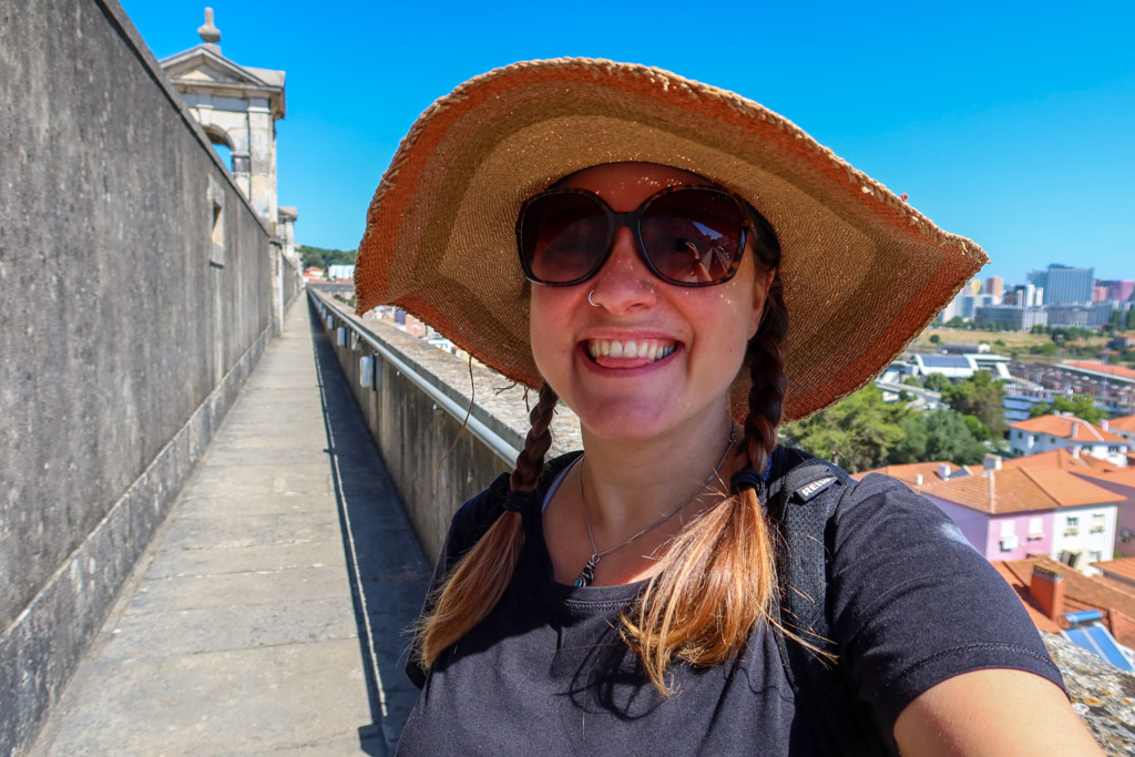 Photo of the author with a broad straw sun hat with braids and sunglasses standing atop the Lisbon Aqueduct