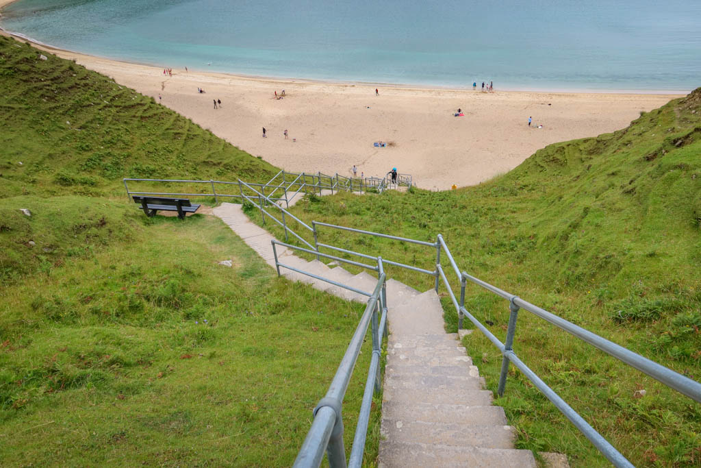 A long series of steps leads steeply downhill to a sandy beach in a hidden cove