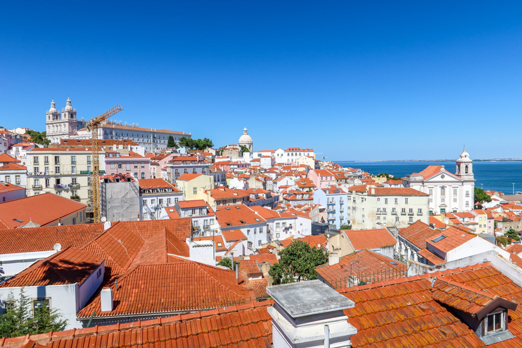 View of red-tiled roofs in Lisbon's Alfalma neighborhood and the Tagus River in the distance