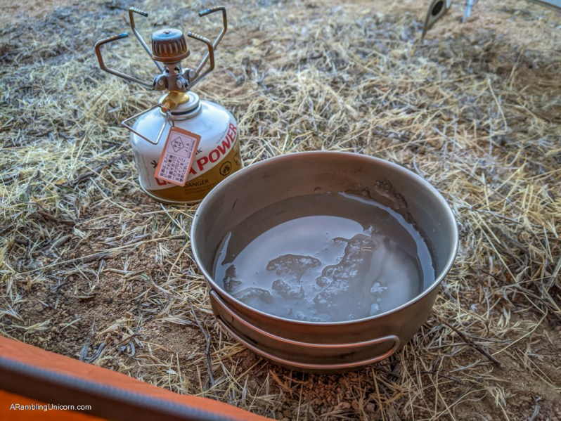 Cooking pot with partially frozen slushy water in it next to a backpacking stove affixed to a small propane canister in the tent vestibule.