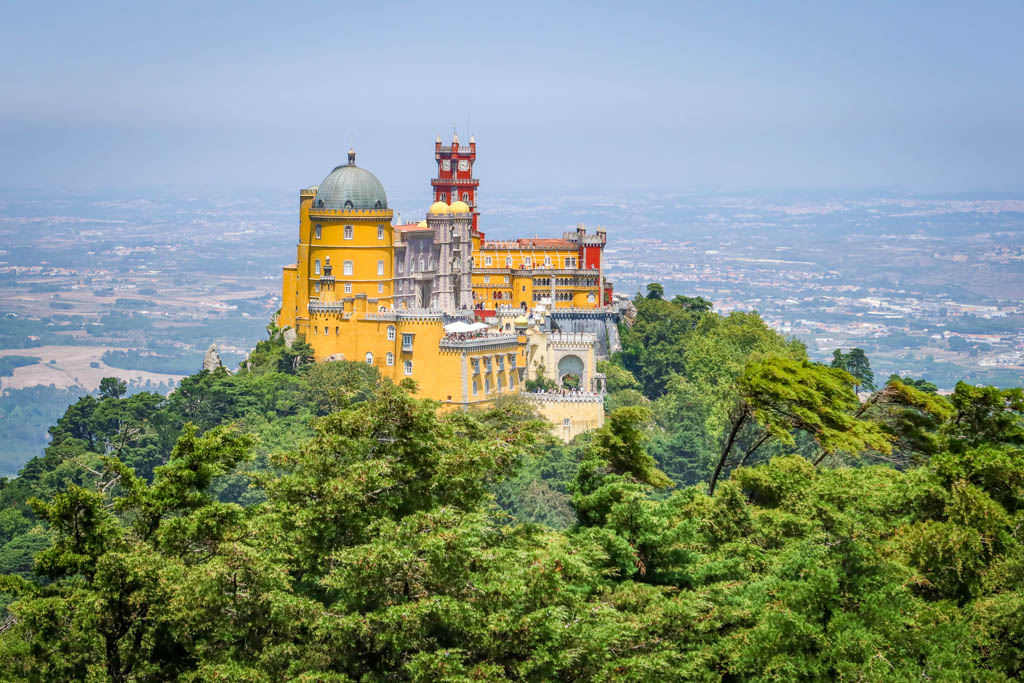 A distant view of Pena Palace perched high on a hill overlooking Sintra. The place is painted a distinctive bright yellow and red color scheme.